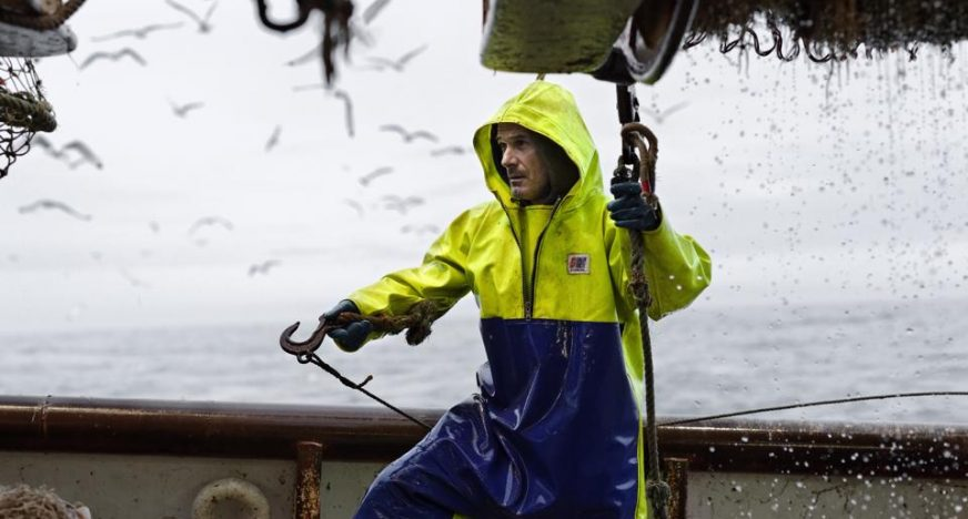 French fisherman on a trawler wearing Stormline fishermans oilskin smock and bib and brace