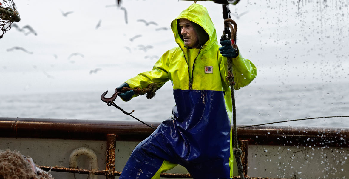Fisherman with fishing hook in hand wearing Stormline foul weather jacket