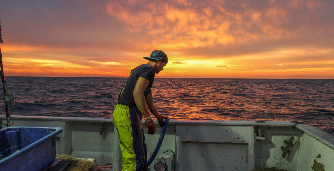Fisherman wearing foul weather rain suit on deck at sunset