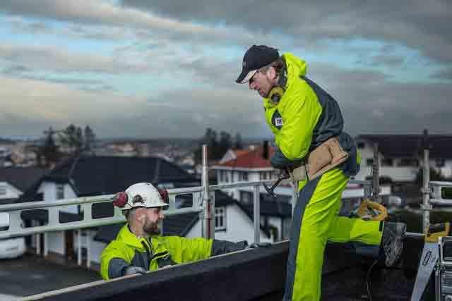 Builders wearing industrial wet weather bib and braces