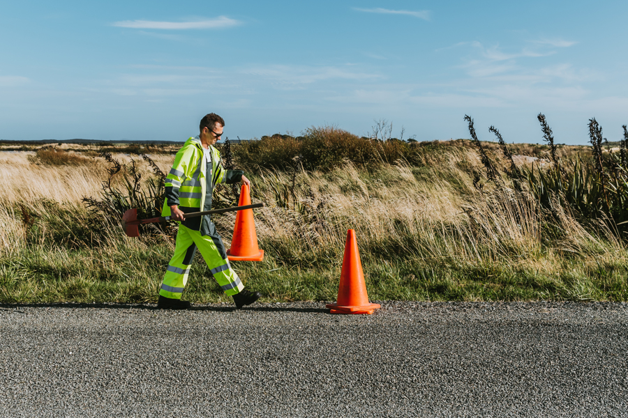 Road worker carrying road cone