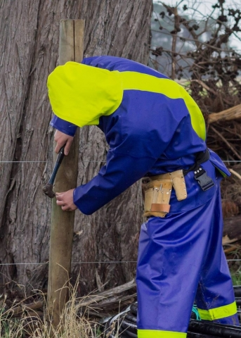 Farmer fixing fence
