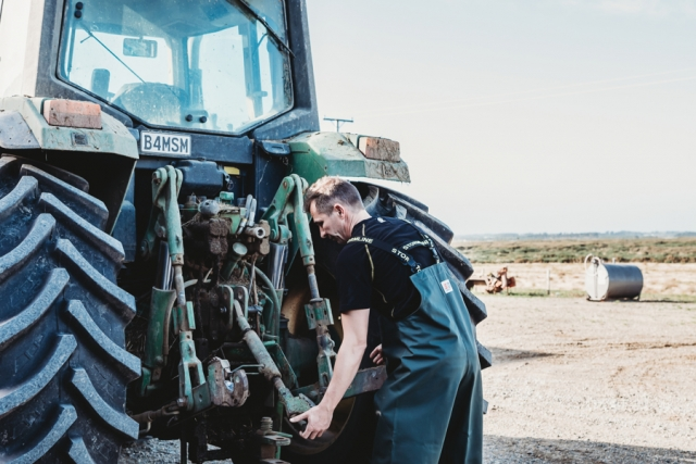 Man in farming waterproof bib and brace fixing a tractor